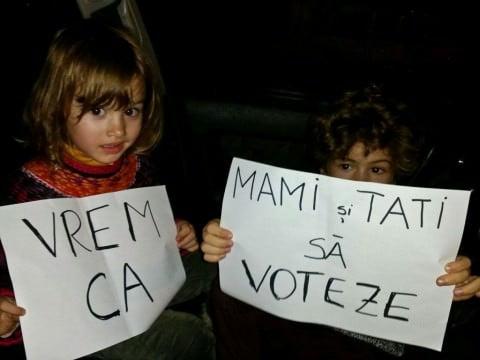 Eliza şi David, fotografiaţi la Paris după 6 ore de aşteptare împreună cu părinţii lor în faţa unei secţii de votare (Sursa foto)